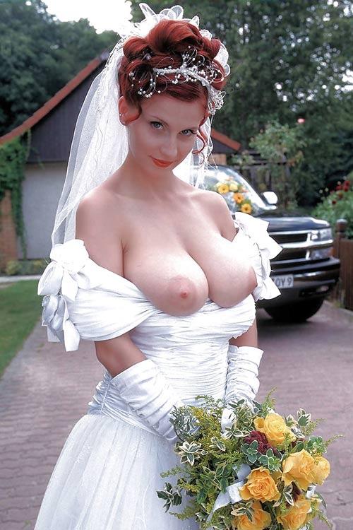 Rousse en robe de mariée aux gros seins à l'air